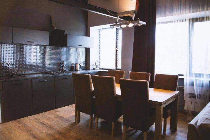 Szerokie ujęcie na drewniany stół z drewnianymi krzesłami stojącymi nieopodal zasłoniętego okna w kuchni