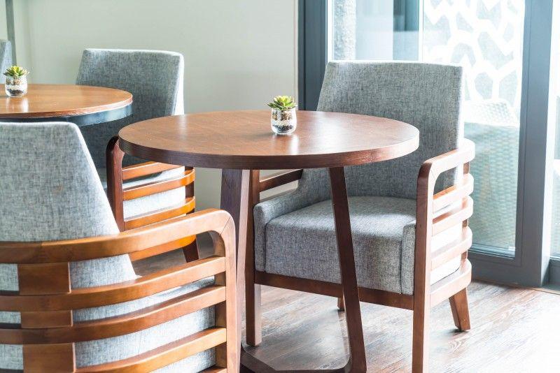 Drewniane stoliki z dosuniętymi drewnianymi fotelami